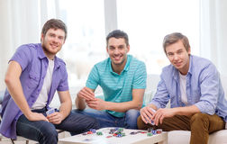 Happy three male friends playing poker at home Royalty Free Stock Images