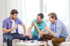 Happy three male friends playing poker at home Stock Photo