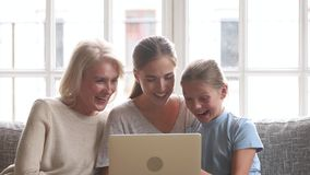 Happy three women generation family watching cartoons on laptop. Happy three women generation family grandma mother and cute child daughter watching cartoons on stock video