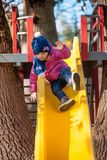Happy three-year baby girl in jacket on slide stock photo