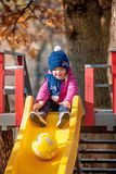 Happy three-year baby girl in jacket on slide royalty free stock images