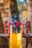 Happy three-year baby girl in jacket on slide stock images