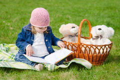 Happy three year old girl reading a book on a picnic Stock Image