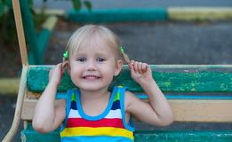 Happy three year old little European blond girl smiling and holding herself for pigtails Royalty Free Stock Image