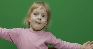 Happy three years old child. Cute girl making faces. Chroma Key. Brown eyes. Green screen. Chroma Key stock photo