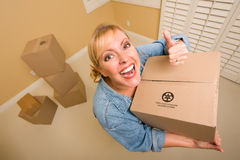 Happy Thumbs Up Woman Moving Boxes. Excited Woman with Thumbs Up and Moving Boxes in Empty Room Taken with Extreme Wide Angle Lens Stock Photography