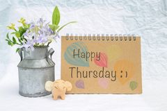 Happy Thursday on design notebook cover with smiling elephant clay and tin flower pot. On blurred background royalty free stock photography
