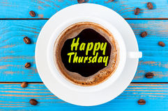 Happy thursday word on coffee cup at blurred blue wooden background with beans Stock Photography