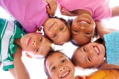Happy time. Below view of happy children embracing each other and smiling at camera Royalty Free Stock Photo
