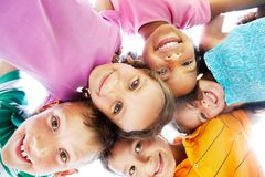 Happy time. Below view of happy children embracing each other and smiling at camera Stock Image