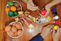 Happy time of family members are painting colorful eggs with a paintbrush and palette for preparing happy Easter day. Royalty Free Stock Photos
