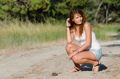 Happy time of a lady outside. She is wearing jean shorts and blouse sitting on legs in the middle of a dirty road looking away. Forest with pines as background Stock Image