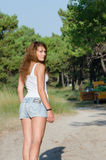 Happy time of a lady outside. She is wearing jean shorts and blouse standing with her back looking over shoulder, under of pine tree. Forest with pines and old Stock Photos