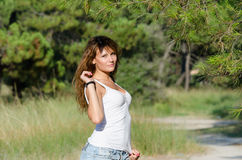 Happy time of a lady outside. She is wearing jean shorts and blouse standing under of pine tree. Forest with pines as background, horizontal picture Stock Photos