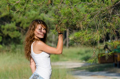 Happy time of a lady outside. She is wearing jean shorts and blouse standing under of pine tree. Forest with pines and old car as background, horizontal Stock Photo