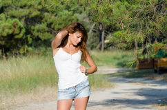 Happy time of a lady outside. She is wearing jean shorts and blouse standing under of pine tree. Forest with pines and old car full with watermelons as Royalty Free Stock Images