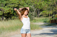 Happy time of a lady outside. She is wearing jean shorts and blouse standing under of pine tree hands over and behind head. Forest with pines and old car as Stock Photography