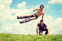 Happy time. Happy men overcomes another men with fluffy clouds in background Stock Images