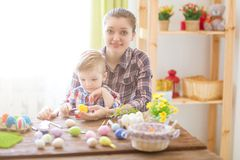 Happy time while painting easter eggs. Easter concept. Happy mother and her cute child getting ready for Easter by painting the eg Royalty Free Stock Image