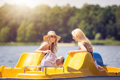 Happy time. A photo of two beautiful women swimming paddle boat at the lake. They're laughing Stock Photos