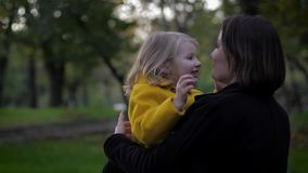 Happy time, sensitive mother carefully plays with her charming daughter in meadow in autumn park during family vacation