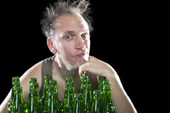 The happy tipsy man near empty beer bottles Royalty Free Stock Image