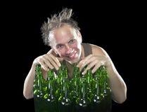The happy tipsy man near empty beer bottles Royalty Free Stock Photos