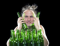 The happy tipsy man near empty beer bottles Stock Photography