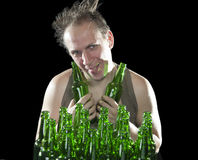 The happy tipsy man near empty beer bottles Stock Images