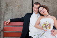 Happy and tired couple. Happy bride sits on a bench with her new husband, after the wedding Stock Images