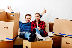 Happy tired couple sitting on couch in new home with cordboard boxes around Royalty Free Stock Photo