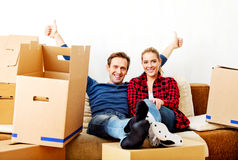 Happy tired couple sitting on couch in new home with cordboard boxes around.  royalty free stock image