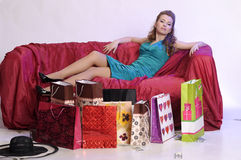 Happy and tired woman resting after shopping. On the sofa with a large Number of shopping bags in front of him Royalty Free Stock Photo