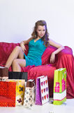 Happy and tired woman resting after shopping. On the sofa with a large Number of shopping bags in front of him Royalty Free Stock Image