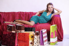 Happy and tired woman resting after shopping. On the sofa with a large Number of shopping bags in front of him Royalty Free Stock Images