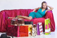 Happy and tired woman resting after shopping. On the sofa with a large Number of shopping bags in front of him Stock Photos