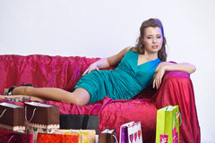 Happy and tired woman resting after shopping. On the sofa with a large Number of shopping bags in front of him Stock Images