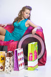 Happy and tired woman resting after shopping. On the sofa with a large Number of shopping bags in front of him Stock Image