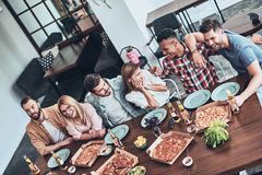 Happy to be around. Top view of young people in casual wear talking and smiling while having a dinner party in the restaurant royalty free stock photos