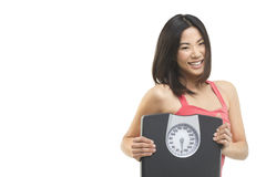 Happy to be healthy. Beautiful Asian woman holding a weight scale Royalty Free Stock Photo