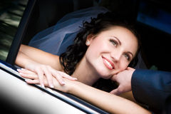 Happy to be his bride. Happy bride looks out of the car royalty free stock photo
