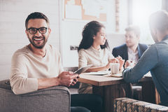 Happy to be a part of great team. Cheerful young handsome men looking at camera with smile while sitting at the office table on business meeting with his royalty free stock photography