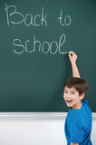 Happy to come back. Cheerful little schoolboy writing on the bla Royalty Free Stock Image