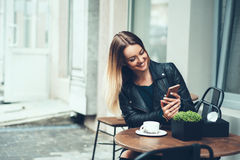 Always happy to communicate with friends. Beautiful young woman sitting in cafe typing message to her friend while drinking taste stock images