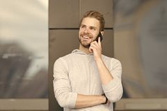 Happy to hear you. Man bearded walks with smartphone, urban background. Man pleasant smiling face speaks on smartphone stock photo
