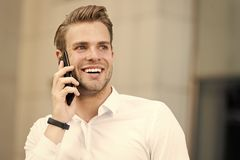 Happy to hear you. Man well groomed speak mobile phone urban background. Businessman cheerful call friend. Friendly stock photo