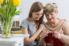 Happy to see her continuing her hobby. Close-up of a cheerful granddaughter cuddling her grandmother who is doing knitwork Royalty Free Stock Photo