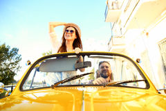 Happy to travel together. Joyful young couple smiling while riding in onvertible royalty free stock images