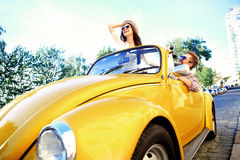 Happy to travel together. Joyful young couple smiling while riding in onvertible royalty free stock image