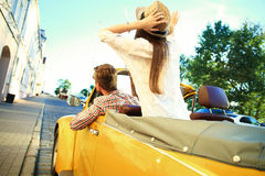 Happy to travel together. Joyful young couple smiling while riding in onvertible Stock Photos